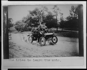 "Dating and the automobile, c. 1907. This photograph is one of a series created to accompany the 1905 song ""In My Merry Oldsmobile."" ""She tries to learn the auto"" is a line from the song. Complete lyrics and original recordings are available online and feature the slang of dating at the turn of the century."