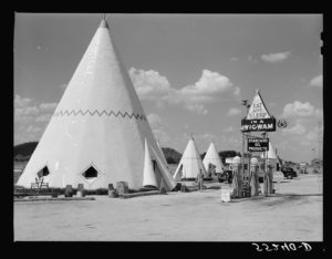 Motel for tourists along state route before construction of federal interstate highways, 1940. Wigwam Village Inn #2 in Cave City, Kentucky near Mammoth Cave National Park. The motel is located on the Dixie Highway, a highway constructed for automobiles between 1915 and 1927, before the Federal-Aid Highway Act of 1956 authorized the construction of limited-access highways that bypassed many towns and tourist attractions. This motel is still open to visitors. There were seven original Wigwam Villages along tourist routes in Alabama, Florida, Louisiana, Arizona, and California; the other two operating motels are located on U.S. Route 66. Photo by Marion Post Walcott. July 1940. Farm Security Administration - Office of War Information Photograph Collection. Courtesy of the Library of Congress.