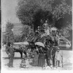 Crowded stagecoach - large group on top, others standing in front, 1877